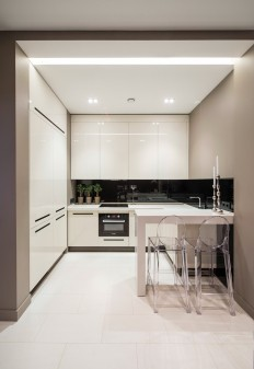 Tiny Small Compact white kitchen with floor to ceiling cupboards and black splashback. on Inspirationde