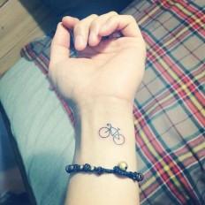 Small minimalist bike tattoo on the left inner wrist.Done by Hongdam