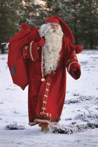 Christmas...the most wonderful time of the year / Santa Claus dressed in a traditional Finnish costume, totes a bag of toys in Rovaniemi, Finland